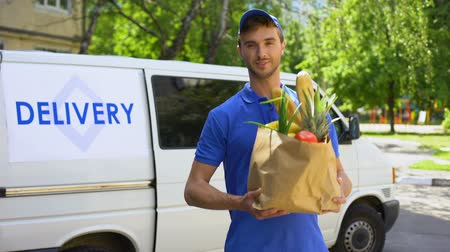 disposição : Delivery company worker holding grocery bag, food order, supermarket service Stock Footage