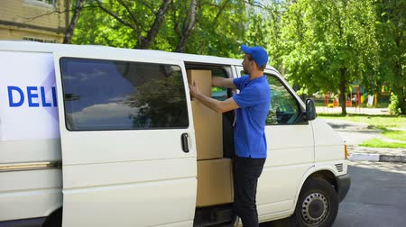 доставка : Postal office worker taking parcel box from delivery van and showing thumbs up