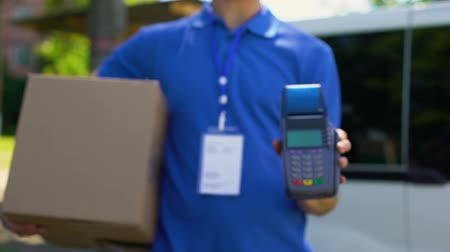 payment terminal : Deliveryman holding box and payment terminal, credit card device.