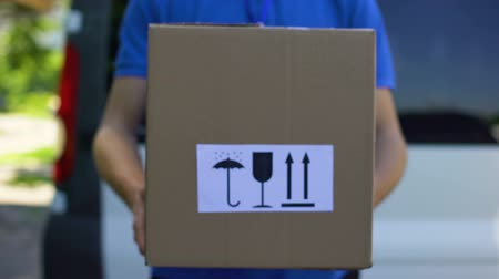 törékeny : Courier in uniform holds box with keep dry, fragile, this way up signs, service