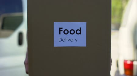 ileri : Food delivery courier in uniform holding cardboard box, shopping online service Stok Video