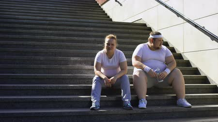 жирный : Fat couple sitting on stairs, exhausted after physical trainings, togetherness