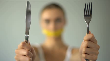 anorexia : Girl closed mouth with tape-line, holding fork and spoon, diet concept.