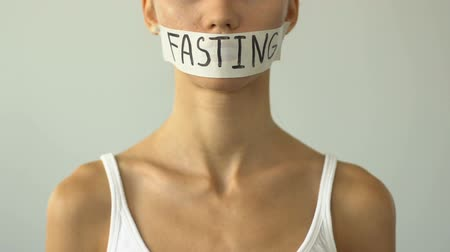 self harm : Fasting written on taped mouth of slim girl, concept of malnutrition, anorexia.
