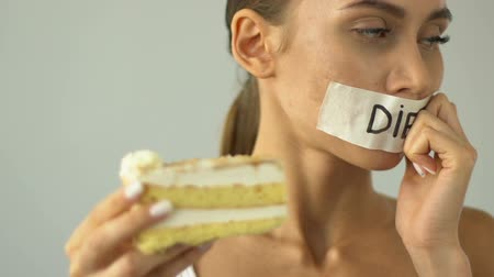 тощий : Closeup of girl on diet wants cake, biting piece, temptation, high-calorie food Стоковые видеозаписи