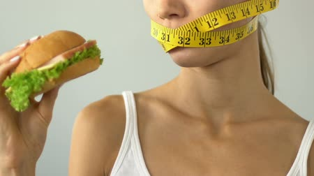 anorexia : Female mouth wrapped with tape-line, girl wants burger but afraid of calories Stock Footage