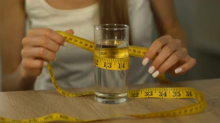 bulimia : Skinny woman measuring glass of water with tape-line as if calculating calories