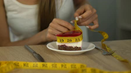 obsession : Slim girl measuring cake with tape-line, concept of counting calories on diet Stock Footage