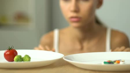 bulimia : Frustrated girl chooses vegetables or anti-obesity pills, healthy diet vs drugs