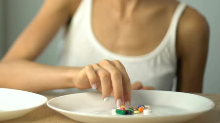 bulimia : Girl taking pills from plate, anti-obesity drugs, loss of appetite, addiction