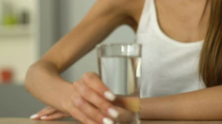 daily : Closeup of female holding glass of water, skin hydration, daily liquid rate Stock Footage