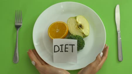 anorexia : Raw diet concept, female hands tied with tape-line holding plate with fruits