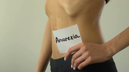 bulimia : Female holding anorexia note, undereating, exhausted body, skinny torso closeup. Stock Footage