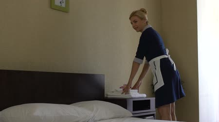 arrumado : Chambermaid allowing herself little pranks joyfully jumping on bed.