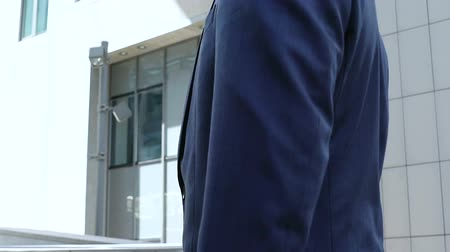 chefia : Handsome office manager in business suit looking at office building, employment