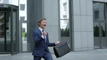 glória : Happy professional lawyer showing success gesture near office building.