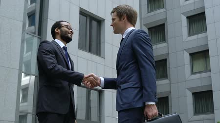 parceria : Successful managers handshaking near office building, cooperation, friendship