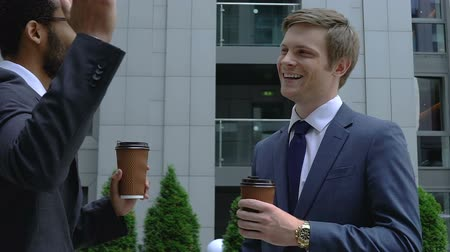 advokát : Successful male lawyers holding cups of coffee talking outside during break