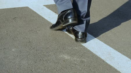 odpowiedzialność : Closeup of male legs walking along arrow, startup, path of ambitious leader