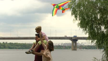 omzunda : Mother flying kite together with son sitting on fathers shoulders, happiness