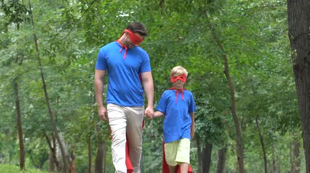 герои : Father and son holding hands, wearing superhero costumes, supportive parent Стоковые видеозаписи