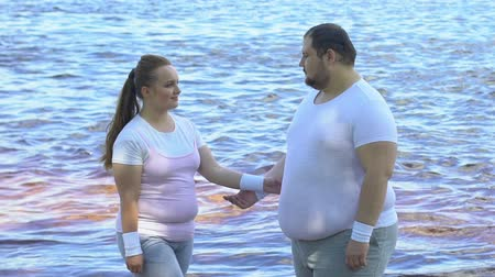 bodyweight : Pretty overweight female hugging her boyfriend near waterfront Stock Footage