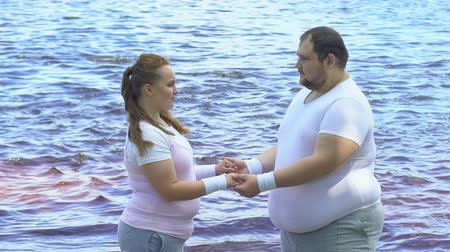 fogyás : Romantic couple of plump people holding hands and looking at each other Stock mozgókép