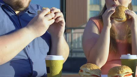 tłuszcz : Plus size couple eating high-calorie burgers in street cafe, obesity problem Wideo