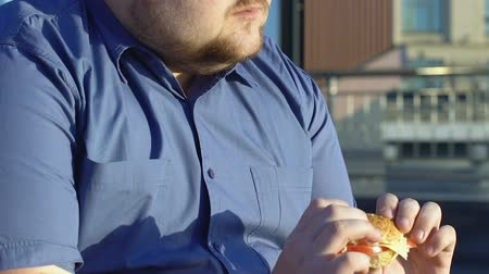 sedentary : Plump male office worker chewing fatty burger outdoors, plus size problem