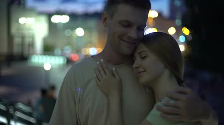 güvenilirlik : Young couple hugging against night city background, sense of reliability comfort