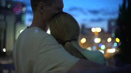 güvenilirlik : Girl leans on guy shoulder, hugging, looking at night city, closeness, safety
