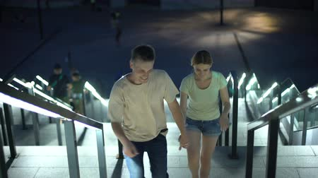 набережная : Carefree couple walking upstairs to embankment to watch illuminated night city