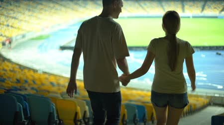 assentos : Football player in casual clothes showing girlfriend empty stadium, dating