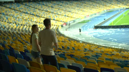 world cup : Couple leaving stadium after football match, empty stadium, interest in sports