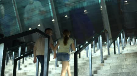 world cup : Couple climbing upstairs to football stadium, fans going to evening match Stock Footage