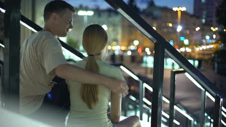 fiable : Couple sitting on stairs, embracing, watching illuminated evening city, love Vidéos Libres De Droits