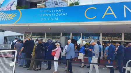 városháza : CANNES, FRANCE - CIRCA MAY 2018: 71st Cannes Film Festival. Cannes film festival visitors in queue, famous annual culture event in France. Stock mozgókép