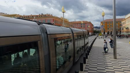eco tourism : NICE, FRANCE - CIRCA MAY 2018: Sightseeing in the city. Train moving through Massena square in Nice, European architecture, cityscape