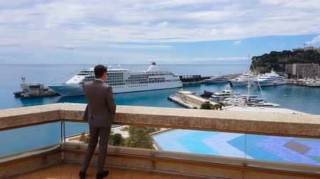 náutico : NICE, FRANCE - CIRCA MAY 2018: People in the city. Young businessman in suit talking on phone, looking at ships and yachts harbor