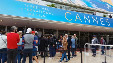 queue : CANNES, FRANCE - CIRCA MAY 2018: 71st Cannes Film Festival. Visitors waiting near Cannes festival entrance, art event, actors award ceremony