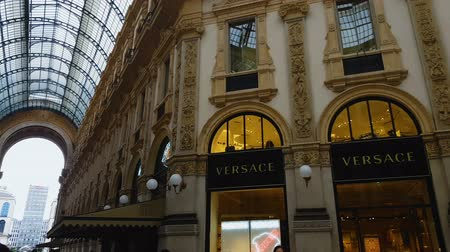 milan fashion : MILAN, ITALY - CIRCA MAY 2018: Shopping in the city. Luxury Prada and Versace fashion boutiques in Italian Galleria Vittorio Emanuele