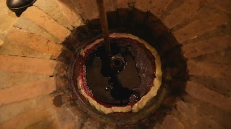 buried : Person taking wine from qvevri buried underground, Georgia winemaking traditions