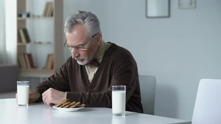 запомнить : Sad grandfather lonely sitting at table with dinner for two, missing his family