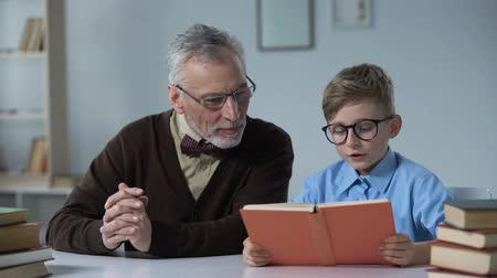 conta : Caring grandfather watching as his little grandson learning to read, helping him