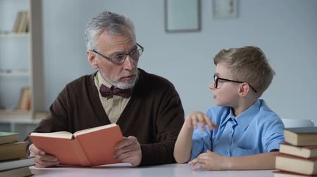conta : Sad boy wants to play instead of boring pastime with grandfather reading book