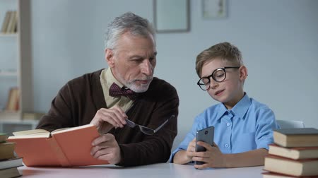 disapprove : Grandfather teaching his grandson about dangers of mobile phone, generation gap.