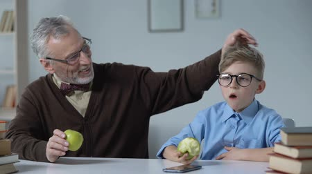 угождать : Boy with sour face eating apple, grandfather teaching healthy nutrition to kid Стоковые видеозаписи