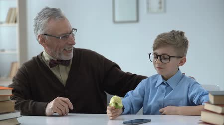 schoolkid : Smart kid with pleasure chewing juicy apple, stocking with vitamins and calcium Stock Footage