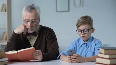 disapprove : Senior man reading and looking at his grandson playing games on phone, leisure Stock Footage