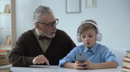 gritar : Senior man criticizing grandson, boy in earphones ignoring him, generation gap